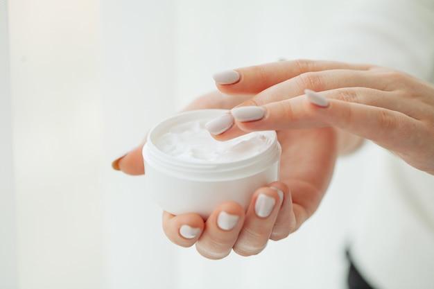 Cuidados com a pele das mãos. close-up de mãos femininas, segurando o tubo de creme, mãos de mulher bonita com unhas de manicure natural, aplicar creme para as mãos cosmético na pele macia e sedosa e saudável