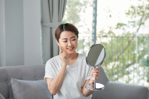 Cuidados com a pele de beleza. linda jovem asiática tocando o rosto diante do espelho