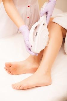 Cuidados com a pele. depilação nas pernas, procedimento a laser na clínica. esteticista remove o cabelo em belas pernas femininas usando um laser
