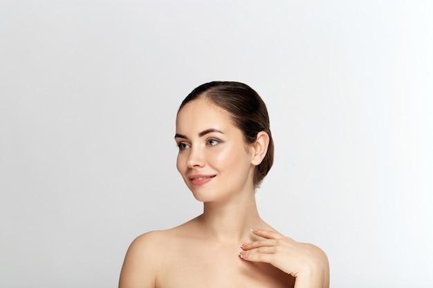 Cuidados com a pele do rosto da mulher. closeup linda mulher sexy com maquiagem profissional perfeita, tocando sua pele lisa suave, pura e limpa. rosto acariciante atraente modelo feminino. cosméticos de beleza.
