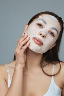 Cuidados com a pele do rosto de beleza. mulher aplica uma máscara hidratante de pano no rosto. modelo de menina com máscara cosmética. tratamento facial