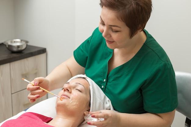Cuidados com a pele do rosto. esteticista aplicando máscara de óleo de beleza no rosto usando uma escova no salão do spa
