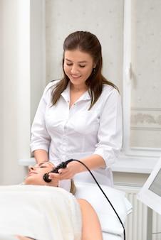 Cuidados com a pele do rosto. jovem mulher bonita com cabelo escuro recebe procedimento no salão de beleza.