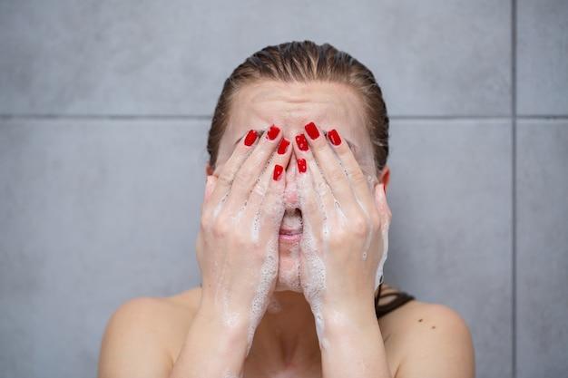 Cuidados com a pele do rosto. mulher aplicando limpador facial no rosto closeup. menina usando produto cosmético de limpeza na pele, lavando o rosto em fundo claro