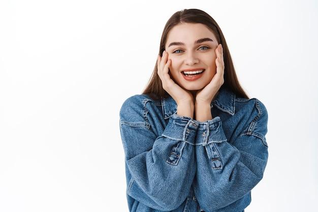 Cuidados com a pele e beleza. linda e feliz adolescente tocando a pele natural pura, limpeza facial fresca, sorrindo satisfeita, encostada na parede branca