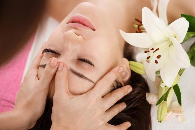 Cuidados com a pele e o corpo. jovem mulher recebendo massagem de rosto. beuty facial