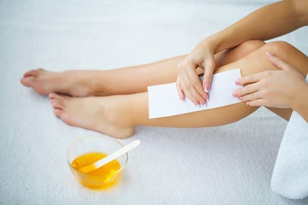 Cuidados com a pele, esteticista encerando a perna de uma mulher
