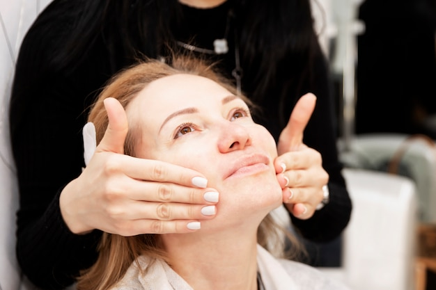 Cuidados com a pele facial em um salão de beleza. mulher adulta loira rosto massageado.