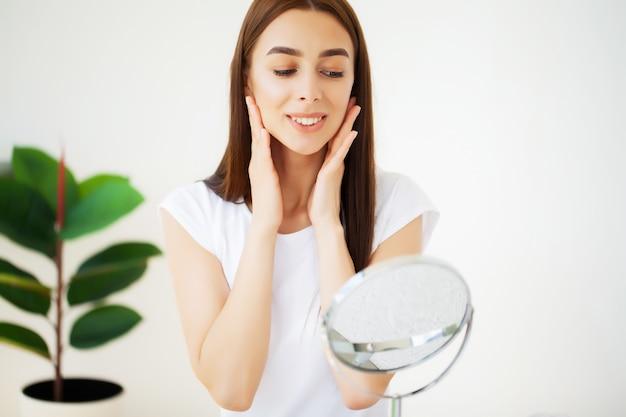 Cuidados com a pele facial, jovem mulher aplica creme facial no banheiro espaçoso de um hotel de luxo