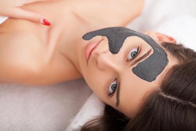 Cuidados com a pele facial. mulher bonita, recebendo máscara cosmética no salão de beleza