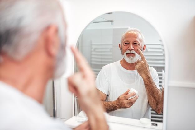 Cuidados com a pele. homem sênior que aplica o creme de cara no banheiro.