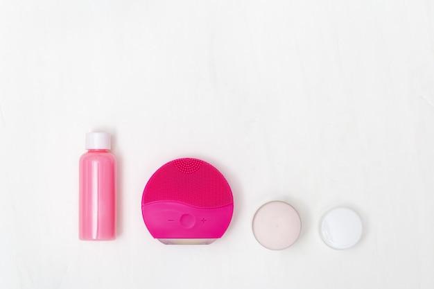 Cuidados com a pele. itens para a limpeza da pele - moda escova vermelha, limpador, hidratante. conceito de blog de beleza.