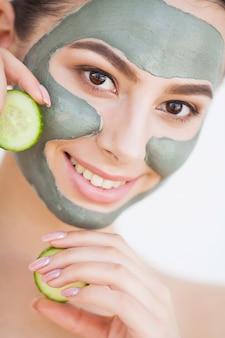 Cuidados com a pele. jovem mulher com máscara de argila cosmética segurando pepino no banheiro
