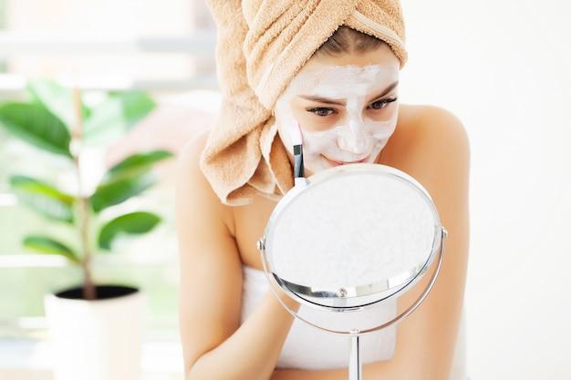 Cuidados com a pele, jovem mulher com pele facial bonita, aplicar a máscara no rosto