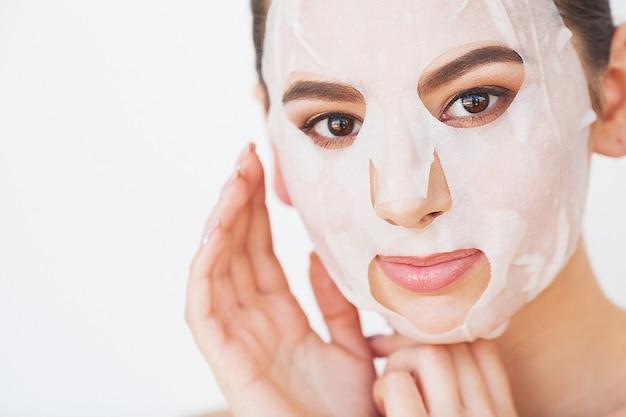 Cuidados com a pele. linda garota com folha de máscara no rosto.