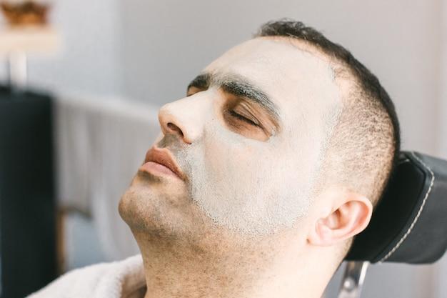 Cuidados com a pele masculina em um salão de beleza. aplicação de máscara de limpeza de argila no rosto de um homem