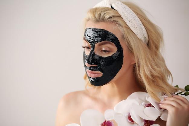Cuidados com a pele. menina segurando uma flor de orquídea perto do rosto