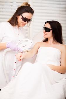 Cuidados com a pele. mulher adulta, com depilação a laser no salão de beleza profissional