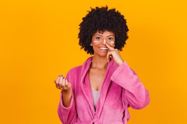 Cuidados com a pele. mulher afro aplicando creme cosmético no rosto isolado em fundo amarelo
