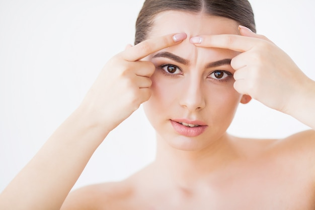 Cuidados com a pele. mulher bonita espremendo espinha no espelho do banheiro.