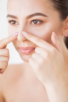 Cuidados com a pele. mulher bonita, espremendo espinhas no espelho do banheiro