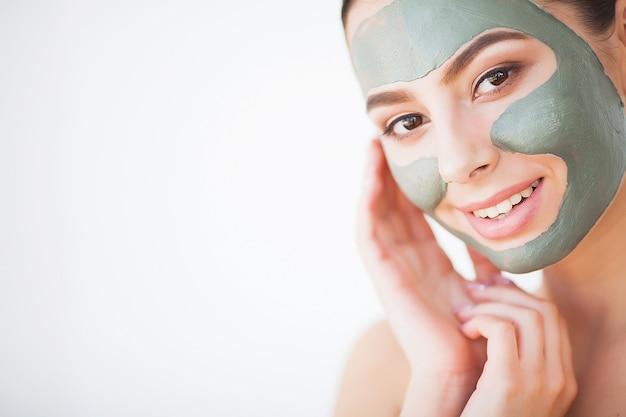 Cuidados com a pele. mulher jovem, com, cosmético, máscara argila, segurando, pepino, em, dela, banheiro