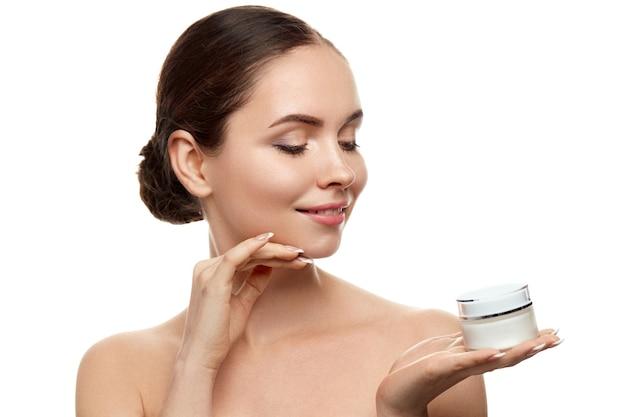 Cuidados com a pele. mulher jovem e bonita com pele fresca limpa, segurando o frasco de creme. cuidado do rosto de beleza. tratamento facial. cosmetologia. beleza e spa