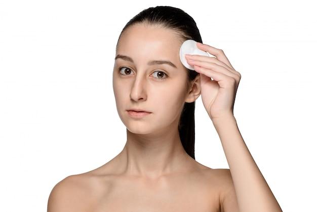 Cuidados com a pele mulher removendo o rosto com cotonete