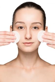 Cuidados com a pele mulher removendo o rosto com cotonetes