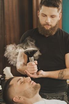 Cuidados com a pele na barbearia. barbeiro barbudo bonito se preparando para usar um pouco de pó de barbeiro em seu cliente