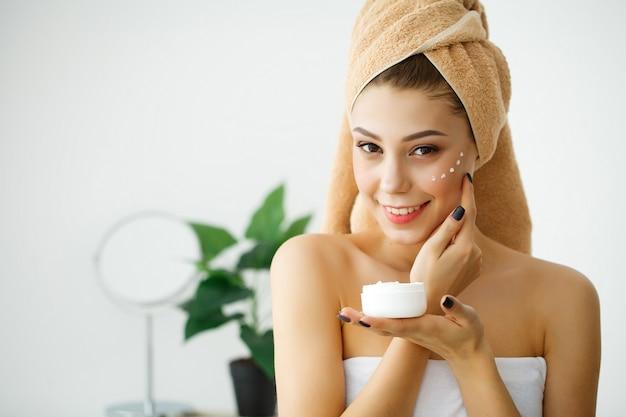 Cuidados com a pele. rosto de beleza de mulher com creme cosmético no rosto