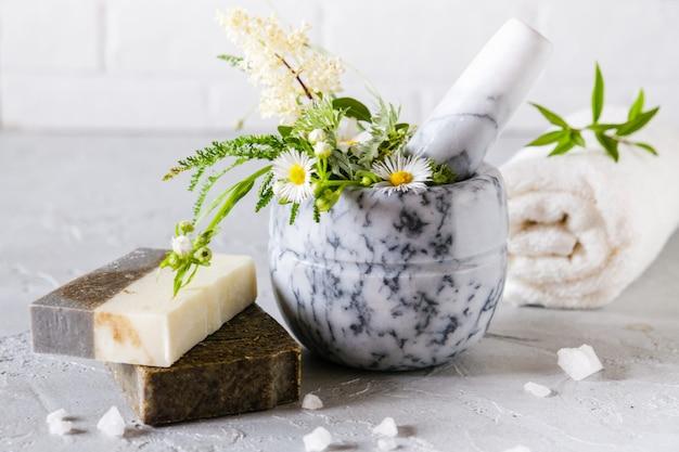 Cuidados com a pele saudável. conceito de spa. sabonete artesanal natural com ervas secas e flores, sal marinho. produtos à base de plantas naturais.