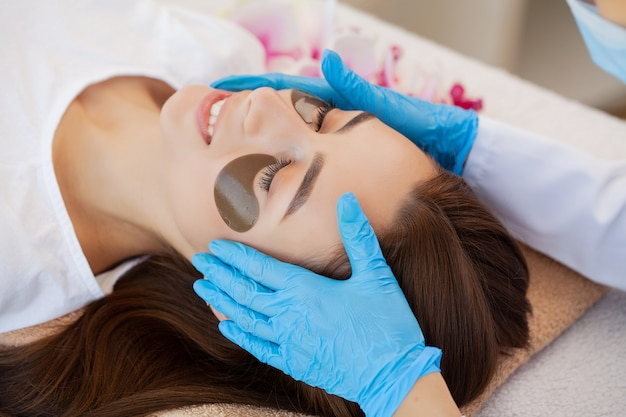Cuidados com a pele sob os olhos, adesivos são aplicados na jovem.