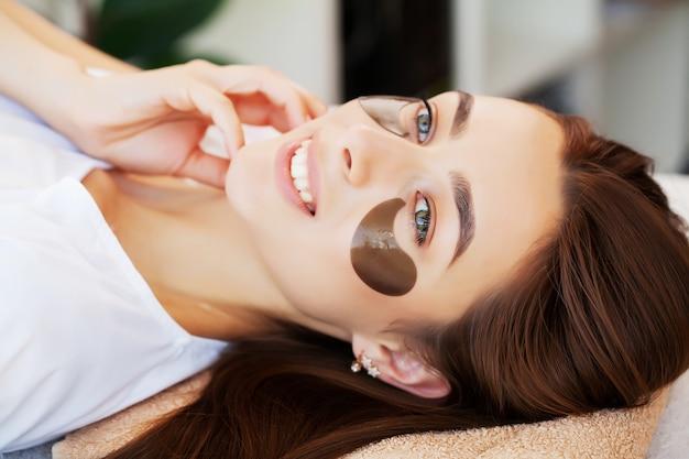 Cuidados com a pele sob os olhos, manchas são aplicadas nos olhos da jovem