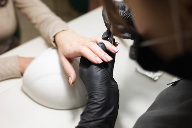 Cuidados com as cutículas durante um processo de manicure em um salão de beleza