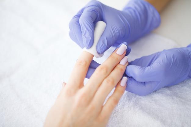 Cuidados com as mãos e unhas. o mestre dá serviços de manicure para o cliente. mãos de mulheres bonitas com manicure perfeita. beleza dia spa manicure