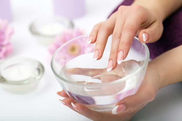 Cuidados com as unhas. close up das mãos bonitas da mulher que mostram os pregos perfeitos pintados com verniz para as unhas vermelho. mãos femininas perto conjunto de ferramentas de manicure profissional. tratamento de beleza. alta resolução