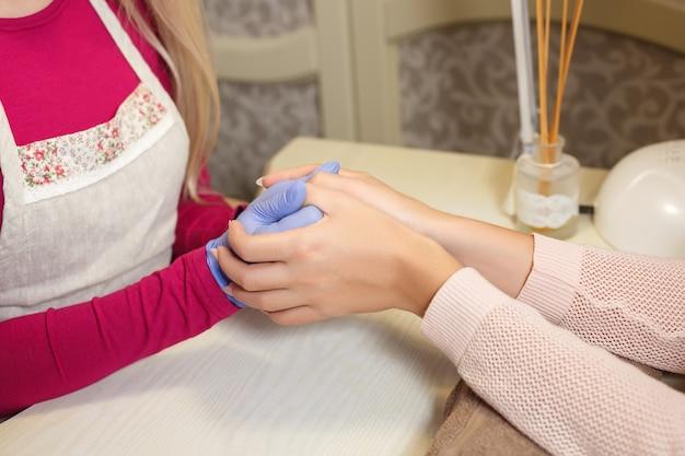 Cuidados com as unhas dos dedos em closeup por especialista em manicure em salão de beleza
