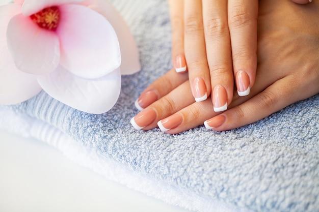 Cuidados com as unhas. unhas de mulher bonita com manicure francesa, no estúdio de beleza