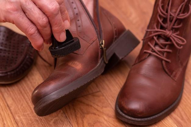 Cuidados com calçados de couro. aplicação de graxa em sapatos marrons.
