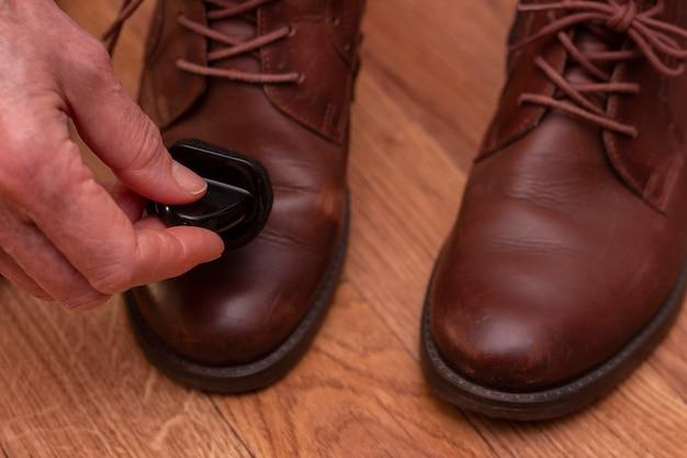 Cuidados com calçados de couro aplicando graxa em sapatos marrons