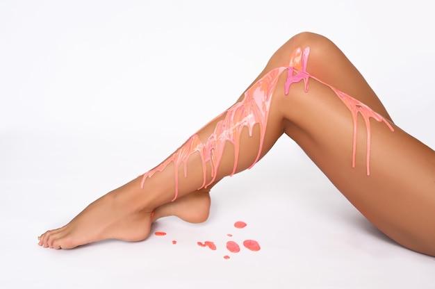 Cuidados com o corpo da mulher. pernas longas e bronzeadas com gotas de tinta acrílica ou cera derretida, pele macia e lisa perfeita, pedicure, unhas saudáveis em fundo branco. conceito de depilação, depilação com cera, beleza e saúde