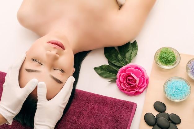 Cuidados com o corpo. tratamento de massagem corporal spa. a menina relaxa no salão spa