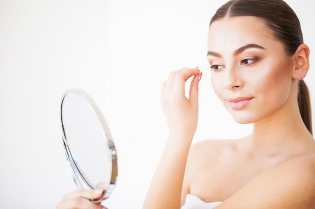 Cuidados com o rosto de beleza. menina com pele saudável, olhando no espelho