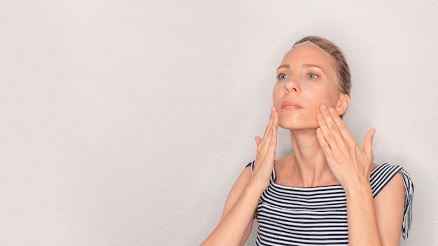 Cuidados com o rosto e tratamentos de beleza. mulher de meia-idade com uma máscara de pano hidratante no rosto em branco com espaço de cópia