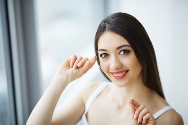 Cuidados com os dentes. mulher de sorriso bonita que flossing os dentes brancos saudáveis.