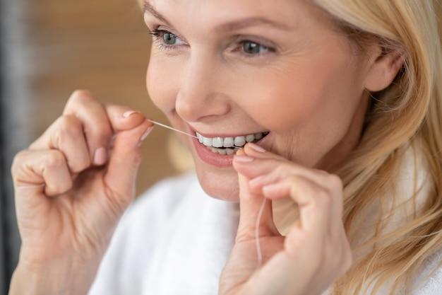 Cuidados com os dentes. uma mulher bonita e sorridente limpando os dentes com um fio dental