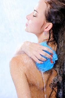 Cuidados corporais por jovem e bela mulher tomando banho - perfil