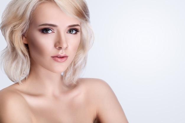 Cuidados de rosto de beleza de mulher. close de jovem atraente feminino tocando a pele facial macia suave fresca. retrato da bela modelo de garota sexy com maquiagem natural, tocando o rosto com a mão.