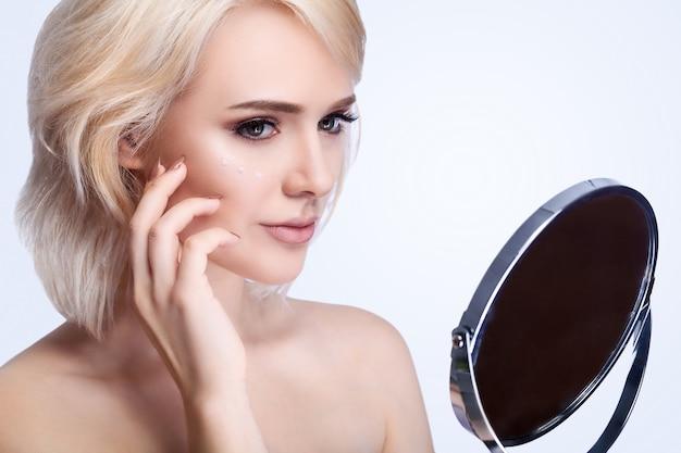 Cuidados de rosto de beleza de mulher. close up da fêmea nova atrativa que toca na pele facial macia lisa fresca. retrato do modelo